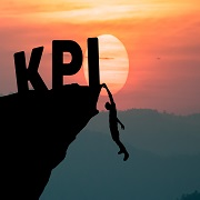 Young businessman climbing the mountain to achieve KPI with sunset background. (to reach key performance indicator)